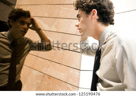 Young aspirational businessman doing up his hair in a golden mirror modern office building in the city. - stock photo