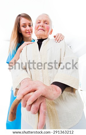 Young assistant and senior woman together in residential home - home care concept. - stock photo