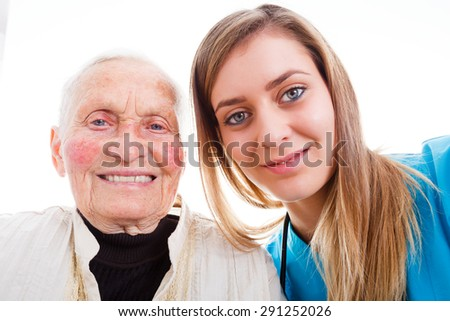 Young assistant taking a selfie with senior woman to send home to the family so they know that everything is good in the residential home. - stock photo