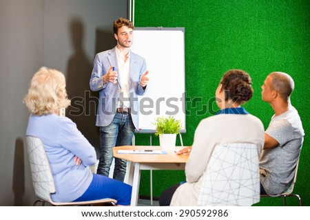 Young associate giving a presentation, using a flip-over white board and markers, to a small project team in an informal setting during a project team meeting in the lounge of a modern office - stock photo