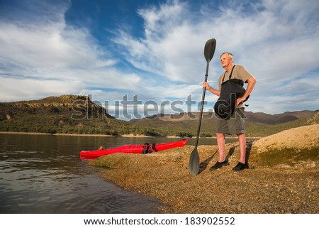 Young at Heart.  Senior Man Surveying the Lake Before a Paddle. Calm Shoreline.