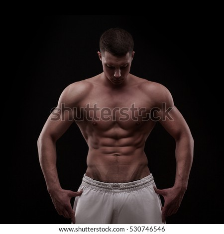young athlete bodybuilder man in white pants looking down. isolated over black background