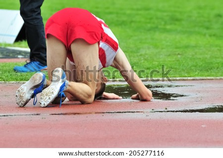 Young athlete falling on the ground after running race. Sporting failure. Training hard to achieve success. No pain no gain. Motivational image for working hard - stock photo