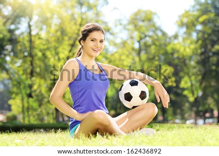 Young athlete female sitting on a green grass and holding a football in a park - stock photo