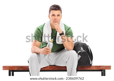 Young athlete holding water bottle seated on bench isolated on white background - stock photo