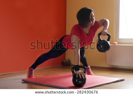 Young athlete in training position with kettle - stock photo