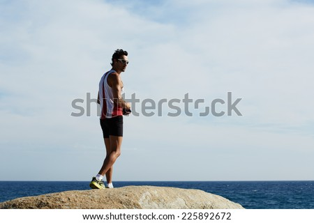 Young athlete listening to music during workout training outdoors, strong fitness man standing on big sea rock while resting after run, male jogger taking breach after workout training on the beach - stock photo