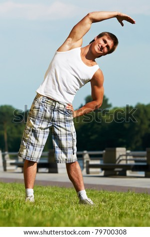 Young athlete man doing stretching warming up before jogging outdoors - stock photo