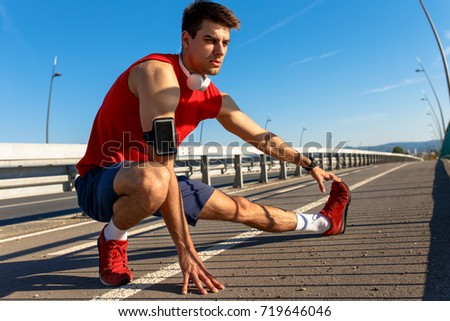 Young athlete man stretching his muscles before running on bridge on sunny day.