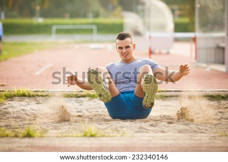 Young athlete performing long jump - stock photo