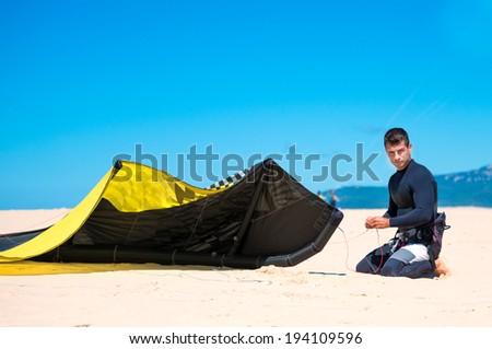 young athlete prepares his kite for kitesurfing training - stock photo