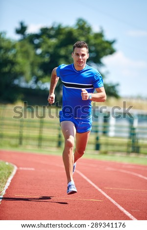 Young athlete runner, sprinting on the stadium track - stock photo