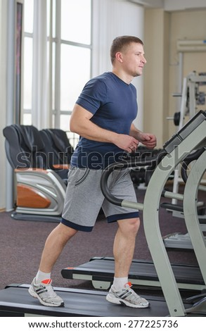 Young athlete running at the gym on the treadmill