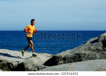 Young athlete running fast jumping over rocks with beautiful sea horizon on background - stock photo