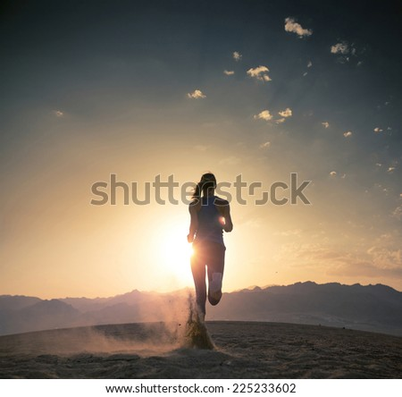 Young athlete running in the desert at sunset - stock photo