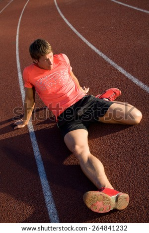 young athlete sits on the track stadium after jogging - stock photo