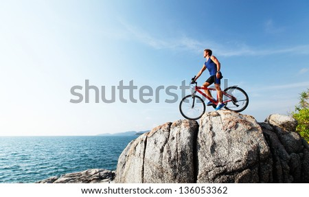 Young athlete standing on a rock with bicycle - stock photo
