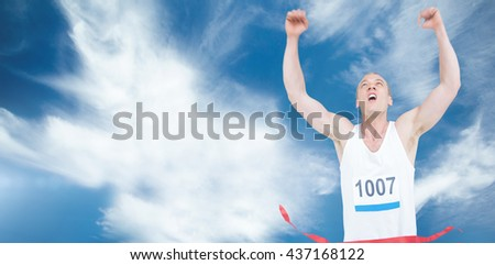 Young athlete winning race against blue sky with clouds - stock photo