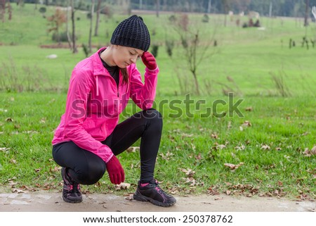 Young athlete woman feeling lightheaded or with headache on a cold winter day in the track of an urban park. - stock photo