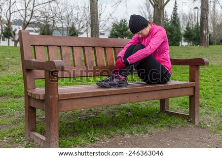 Young athlete woman tired or depressed resting on a bench on a cold winter day in the track of an urban park. - stock photo
