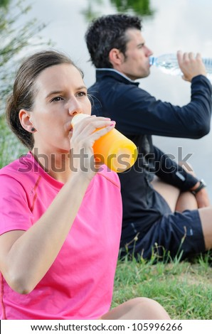 Young athletes drinking and resting after training. Athletes couple sitting in park holding bottle. - stock photo