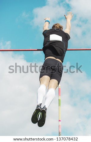 Young athletes pole vault  over the bar seems to reach the sky - stock photo