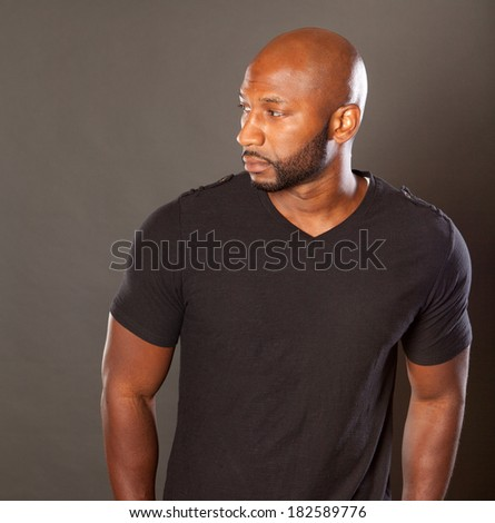 Young athletic black man in a casual pose wearing a dark t-shirt looking at the camera with a sesios attitude / expression looking to the side - stock photo