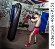 Young athletic boxer training his punches and jabs on a boxing bag in a graffiti clad suburban basement - stock photo