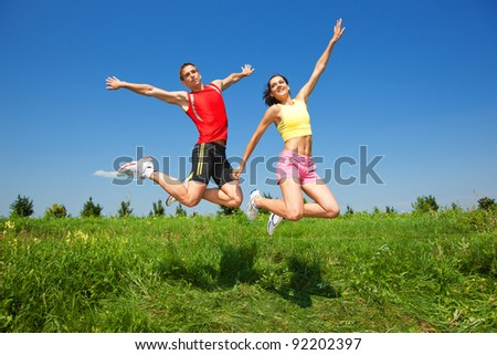 Young athletic Couple jump under blue sky - stock photo
