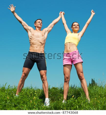 Young athletic Couple smiling under blue sky - stock photo