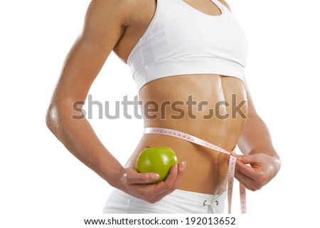 young athletic girl measuring waist measuring tape and holding a green apple, concept of healthy eating, isolated on white background - stock photo