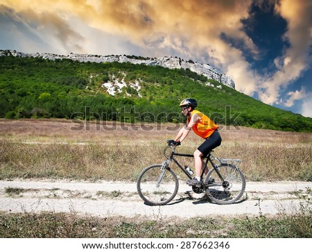 young athletic girl rides a bicycle on a mountain road at sunset - stock photo