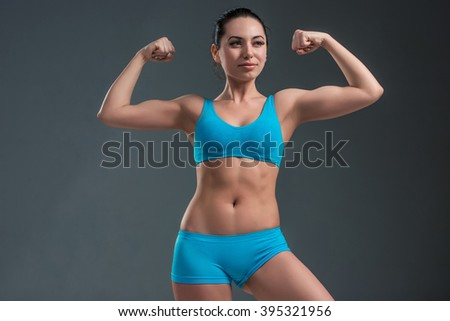 young athletic girl shows muscles