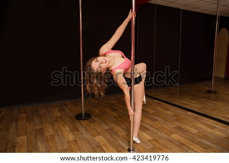 young athletic girl sitting on the splits near the pole in the gym - stock photo