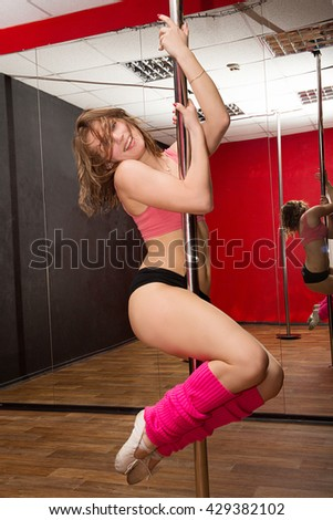 young athletic girl sitting on the splits near the pole in the gym