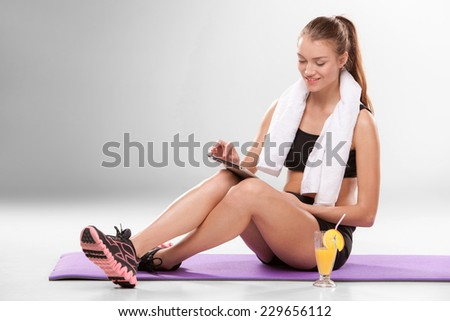 Young athletic girl sitting with laptop with cocktail isolated on gray background. Pause in training