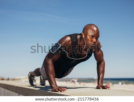 Young athletic man doing push-ups. Fitness model doing outdoor workout. Muscular and strong guy exercising.  - stock photo