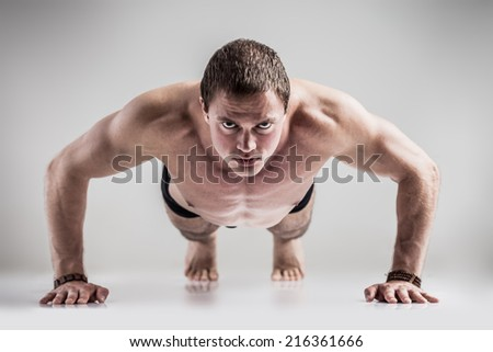 Young athletic man makes push ups exercises on gray background