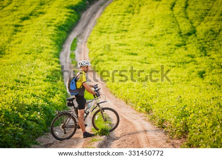 young athletic man on a bicycle rides on the green meadow road - stock photo
