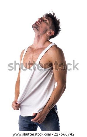Young athletic man pulling down tanktop on ripped muscular torso, isolated on white