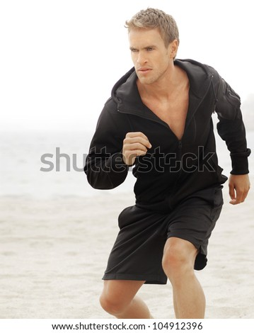 Young athletic man running with determined expression - stock photo