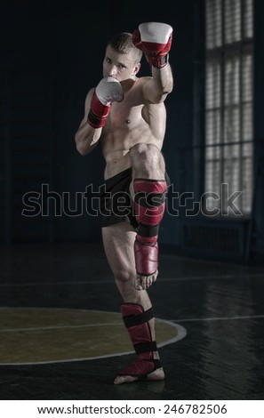 Young athletic man with boxing gloves and a rack - stock photo