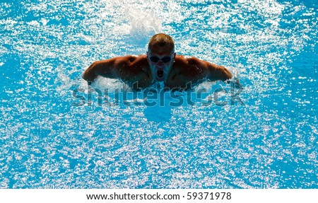 Young athletic man working out swimming in pool - stock photo