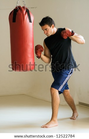 Young athletic man working out with a heavy punching bag. Isolated. - stock photo
