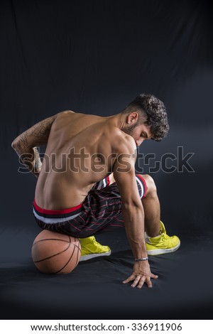 Young athletic shirtless man on dark background sitting on basketball ball, looking down, seen from the back - stock photo