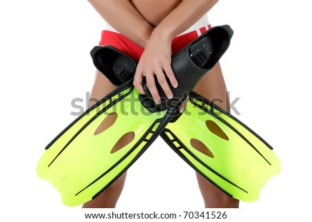 Young athletic swimmer with goggles, covers his swimsuit with the flippers. Body part. Studio shot. White background - stock photo
