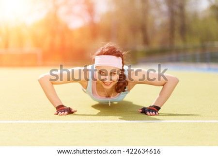 Young athletic woman doing core exercise at the stadium. Smiling caucasian girl doing pushing up on grass - stock photo