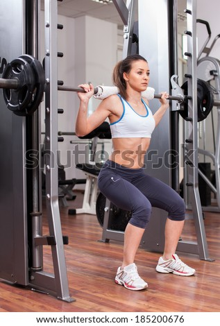 Young athletic woman doing squats with the barbell at the gym