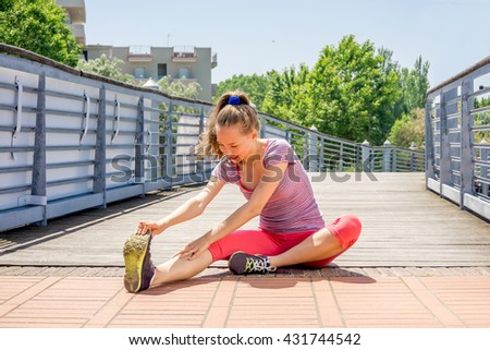 young athletic woman doing stretching and fitness training exercise ready for jogging under   bright sun - concept of healthy active lifestyle wellness and personal sports - stock photo
