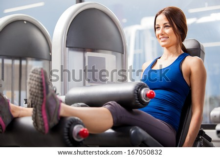 Young athletic woman enjoying her gym routine and working on her leg muscles - stock photo